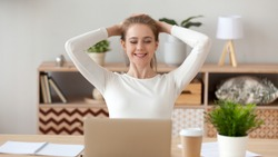 Smiling young woman relaxing leaning back with hands behind head after finished computer work, looking at computer screen, reading good news, successful deal, business achievement, promotion