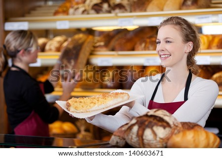 smiling young woman selling cake in bakery