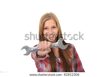 Smiling young woman showing a wrench into the camera