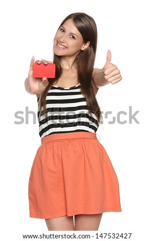 Smiling young woman showing blank credit card and gesturing thumb up, isolated on white background