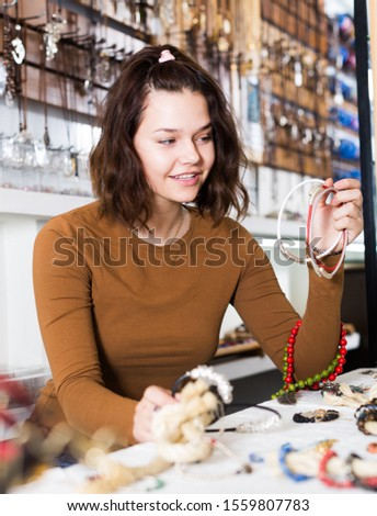 Smiling young woman showing different pendants in the market #1559807783