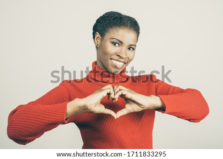 Smiling young woman showing love sign. Cheerful African American lady gesturing and looking at camera. Love gesture concept Stockfoto ©