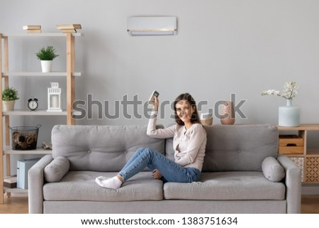 Smiling young woman sit relax on cozy couch in living room turn on air conditioner with remote controller, happy girl rest on sofa at home set comfortable temperature on condition system