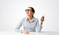 Smiling young woman sits at desk and dreamy looking upward. Portrait of beautiful girl in glasses with bright red lips on white wall background. Human resource and career development concept.