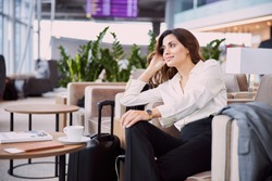 Smiling young woman sitting in comfortable chair in departure lounge stock photo