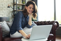 Smiling young woman sitting on sofa with laptop computer and chating with friends.