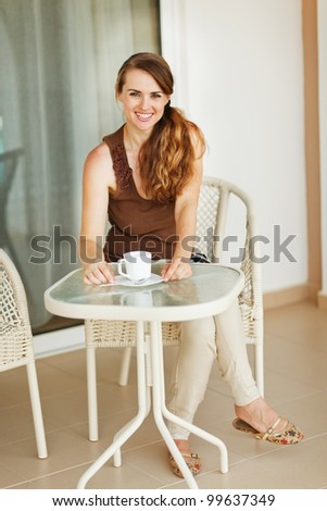 Smiling young woman sitting on terrace and having coffee