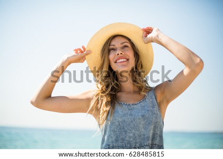 Smiling young woman standing against sky on sunny day