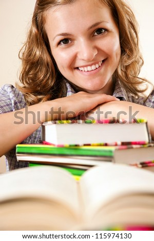 Smiling young woman student with her books on white background.