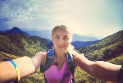 Smiling young woman takes a selfie   in Carpathian Mountains