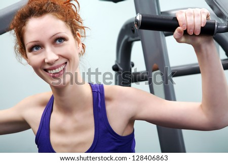 Smiling young woman training on sport machine in gym