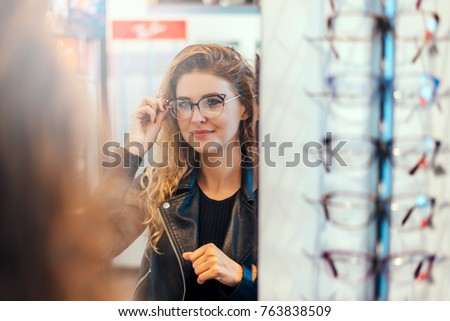 Smiling young woman trying on glasses on mirror in optician. #763838509