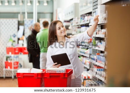 Smiling young woman using a digital tablet for shopping at supermarket