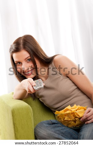 Smiling young woman watching television and eating potato chips