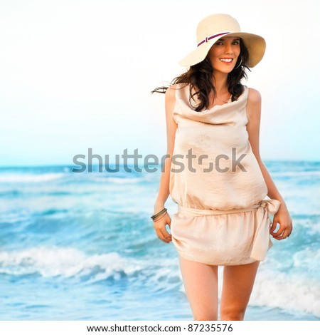 Smiling young woman wearing a straw hat and having fun at the beach