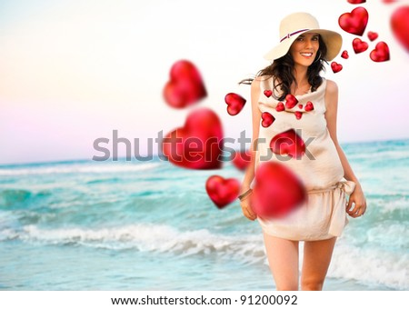 Smiling young woman wearing a straw hat and having fun at the beach. Beautiful red hearts are flying around her