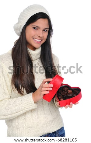 Smiling young woman wearing a white sweater and knit hat opening a box heart of Valentines Day candy. Vertical format isolated over white.