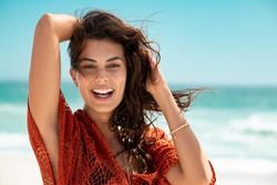 Smiling young woman wearing red lace dress and looking at camera. Beautiful tanned girl enjoying summer vacation at sea. Portrait of stylish carefree woman laughing at the ocean with copy space.