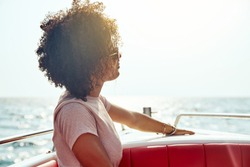 Smiling young woman wearing sunglasses enjoying the ocean view and fresh sea air while sitting on a boat during summer vacation