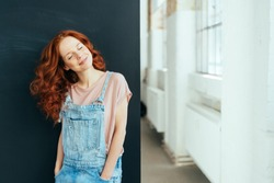 Smiling young woman with a happy serene smile wearing trendy denim dungarees standing with head tilted to the side indoors at home