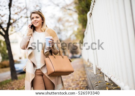 Smiling young woman with a mobile phone. Walking through the park.