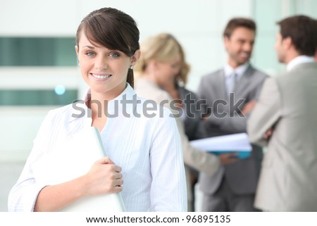 Smiling young woman with colleagues in the background