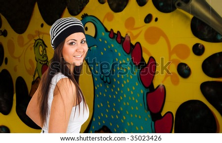 Smiling young woman with graffiti on background