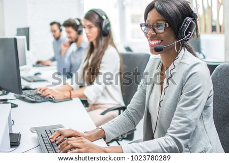 Smiling young woman with headset working in call center. #1023780289