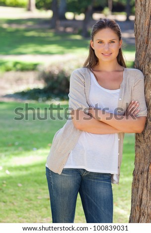 Smiling young woman with her arms crossed leaning against a tree