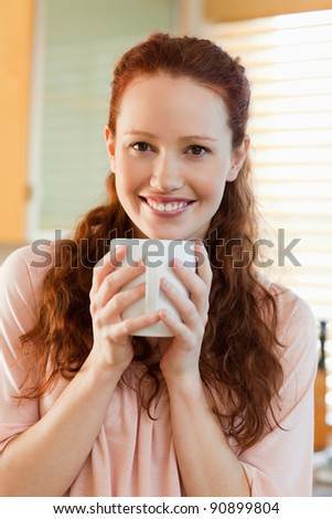 Smiling young woman with her cup of coffee