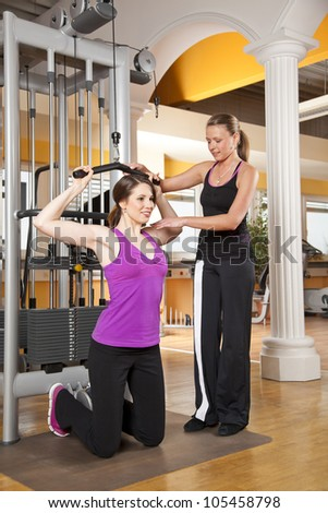 smiling young woman with her female coach training latissimus