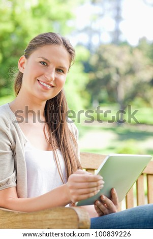 Smiling young woman with her tablet on a park bench