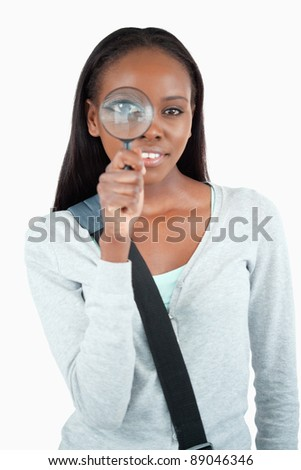 Smiling young woman with magnifier against a white background