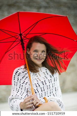 Smiling young woman with open umbrella at hand