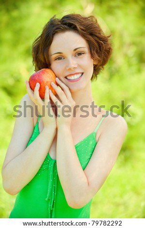 Smiling young woman with red apple