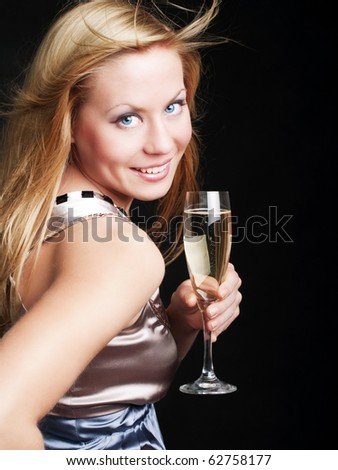 smiling young woman with sylvester champagne over dark background