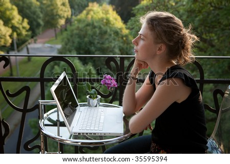 smiling young woman writing on a white modern laptop computer on a balcony in art nouveau