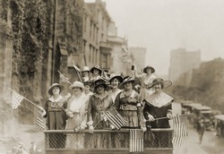 Smiling young women waving flags from the top of an open vehicle in a New York City parade. Ca. 1910-1915.
