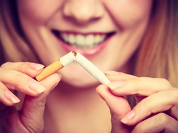 Smilling woman breake down cigarette. Winning with addicted nicotine problems, stop smoking. Quitting from addiction concept. On blue