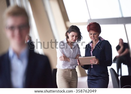Smilling young business woman in front her team blured in background. Group of young business people. Modern bright  startup office interior. #358762049