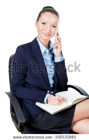 Smilling young business woman sitting on chair and using mobile phone