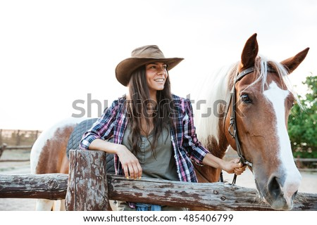 Smilng pretty young woman cowgirl standing with her horse on ranch