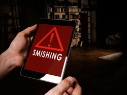 Smishing alert concept. Hands hold tablet with message.