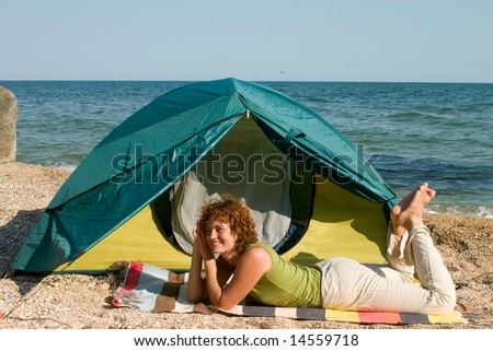 Smniling girl lie near of her tent at seaside