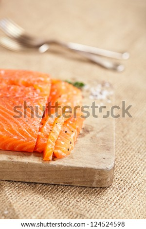 smocked salmon homemade, with spice on wooden board, shallow dof - stock photo