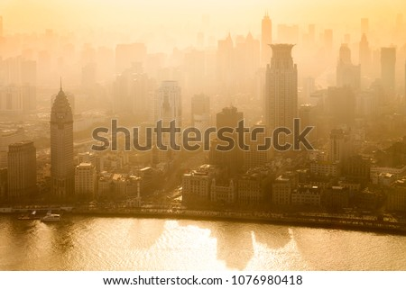 Smog lies over the skyline of Historical architecture and modern skyscraper on the bund of Shanghai city in misty gold lighting sunrise, Shanghai, China vintage picture style