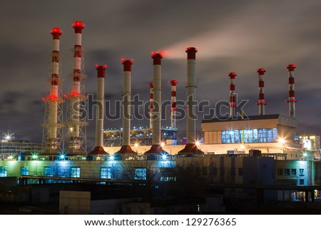 smoke and pipe plant with red lights in the night sky