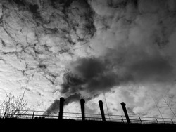 Smoke and steam from huge factory chimneys against cloudy sky. Ecology problems of big city.