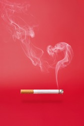 Smoke as question sign and a smoking cigarette on red background.