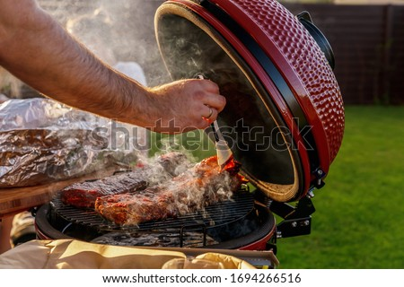 Smoke coming out of red ceramic Barbecue Grill. The man coats pork ribs with barbeque sauce. Picnic in modern homes terrace.
